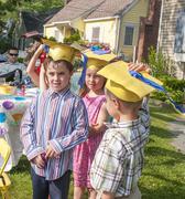 Young children at kindergarten graduation, wearing paper mortar boards Stock Photos