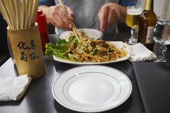 View of person tucking into plate of noodles Stock Photos