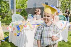 Portrait of young boy at kindergarten graduation, wearing paper mortar board - stock photo