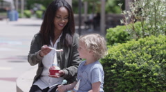 Young woman and boy sitting outside eating ice cream Stock Footage