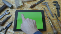 Male hand of craftsman using tablet pc. Different vintage tools lie beside Stock Footage
