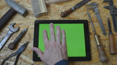 Male hand using tablet pc. Different vintage tools lie beside Stock Footage