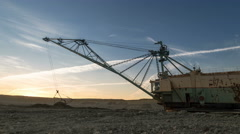 Time lapse. Drag-line excavator loads ore into dump-track. Sunset Stock Footage