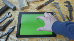 Male hand of artisan craftsman using tablet pc with green screen in workshop Stock Footage