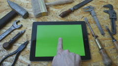 Tablet pc with green screen with carpentry tools in the background Stock Footage