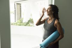 Mature woman holding yoga mat drinking water - stock photo