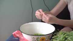 Young hands shelling green peas in the village Stock Footage