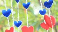 Bunch of handmade paper hearts hanging in the garden on Valentine's Day, HD vdo. Stock Footage