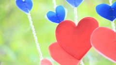 Bunch of handmade paper hearts hanging in the garden on Valentine's Day, HD vdo. - stock footage