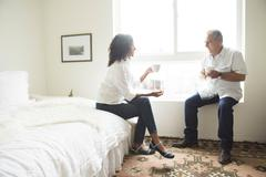 Senior man and wife drinking coffee in bedroom Stock Photos