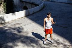 Jogger selecting music on smartphone, Arroyo Seco Park, Pasadena, California, Stock Photos