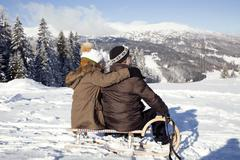 Snow capped mountains and rear view of senior couple sitting on sledge looking Stock Photos