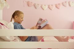 Side view of girl sitting on bed reading magazine - stock photo