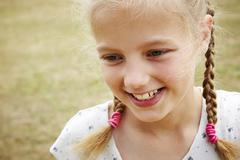 Close up portrait of girl with pigtails looking away smiling - stock photo