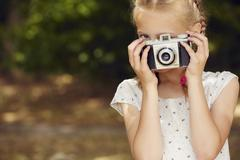 Girls using film camera, looking at camera face obscured - stock photo