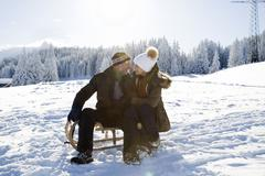 Senior couple on snowy landscape sitting on sledge face to face smiling, Stock Photos