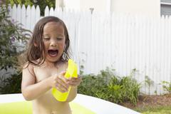 Girl in inflatable pool, excited over toy - stock photo