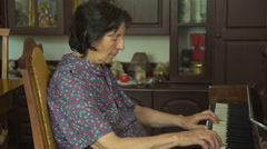 Old woman is playing the piano and looking on a camera Stock Footage
