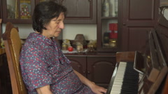 Profile of old woman is playing the piano at home - stock footage