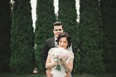 Romantic, fairytale, happy newlywed couple hugging and kissing in a park, trees Stock Photos
