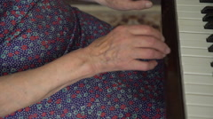 Old woman with wrinkled hands is playing the piano Stock Footage