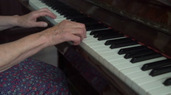 Old cute woman is playing the piano in the home Stock Footage