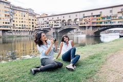 Lesbian couple sitting on arno river bank in front of Ponte Vecchio holding - stock photo