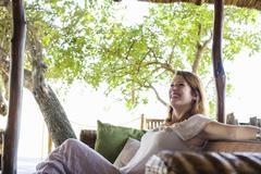 Young woman relaxing on sofa at safari lodge, Kafue National Park, Zambia Stock Photos