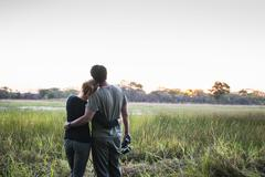 Romantic couple on safari looking out at landscape, Kafue National Park, Zambia - stock photo