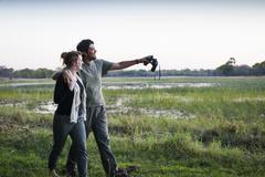 Couple on safari exploring landscape, Kafue National Park, Zambia Stock Photos