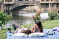 Lesbian couple lying on blanket in front of Ponte Vecchio over river Arno, - stock photo