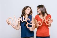 Lesbian couple holding the words you and me face to face smiling - stock photo
