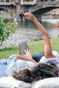 Lesbian couple lying down using smartphone to take selfie in front of Ponte - stock photo