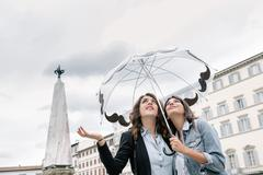 Lesbian couple holding umbrella checking for rain with hand, looking up, Piazza Stock Photos