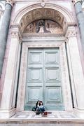 Lesbian couple sitting in oversized church doorway looking at book, Piazza Santa Stock Photos