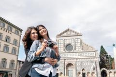 Lesbian couple holding digital camera hugging in front of church, Piazza Santa - stock photo