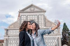 Lesbian couple using smartphone to take selfie in front of church, kiss on Stock Photos