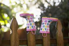 Rubber boots, upturned, on wooden fence posts Stock Photos