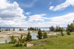Steaming aqua hot spring, with people on boardwalk, Yellowstone. - stock photo