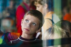 View through glass of young boy on outing looking up thoughtfully - stock photo