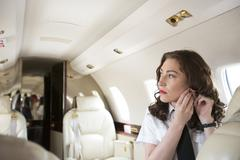Female flight attendant putting on earring in cabin of private jet Stock Photos