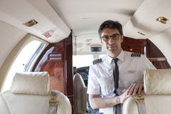 Portrait of male pilot in cabin of private jet Stock Photos