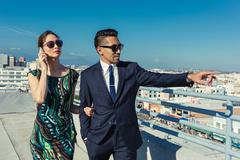 Businessman and businesswoman looking at view on roof terrace, Los Angeles, Stock Photos
