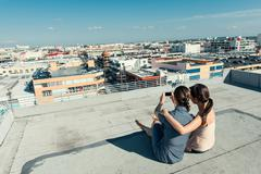 Businesswomen taking selfie with smartphone on roof terrace, Los Angeles, Stock Photos