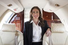 Portrait of female flight attendant on private jet Stock Photos