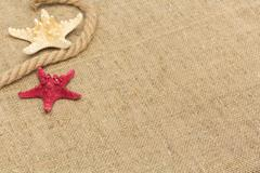 starfish and rope lying on a sackcloth - stock photo