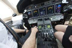 Cropped shot of male and female pilots knees in cockpit of private jet Kuvituskuvat