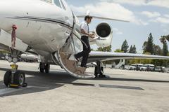 Male private jet pilot stepping from plane at airport Kuvituskuvat