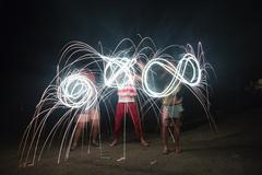 Four adult friends making sparkler patterns in darkness on Independence Day, USA Stock Photos