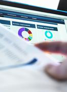 Investor checking performance of financial portfolio online whilst reviewing - stock photo
